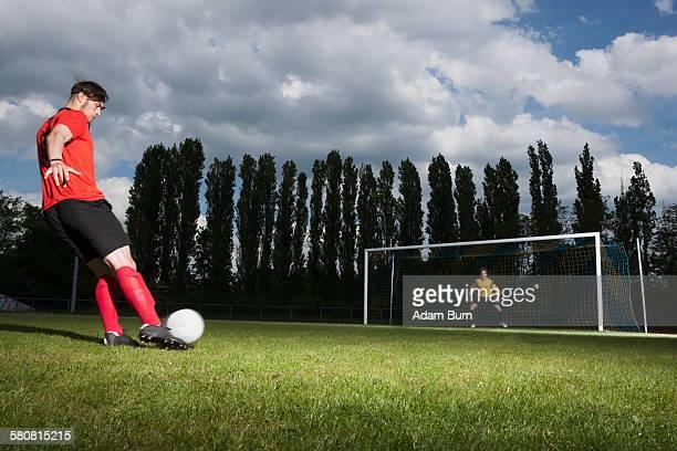 Full length of soccer player kicking ball at goal