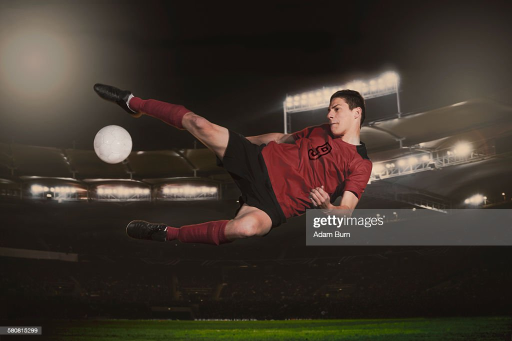 Full length of soccer player kicking ball during match : Stock Photo