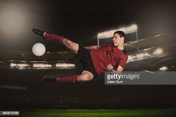 full length of soccer player kicking ball during match - tirare in rete foto e immagini stock