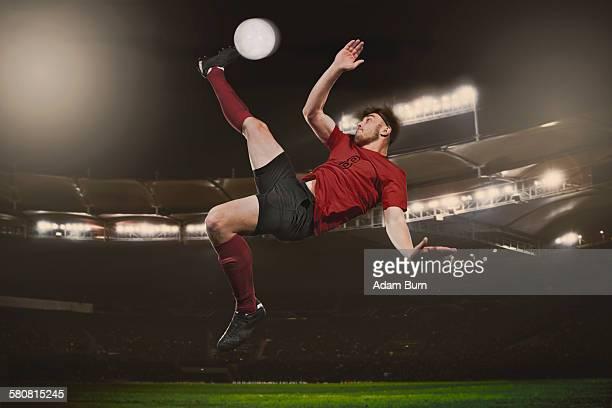 full length of soccer player kicking ball on field - tirare in rete foto e immagini stock