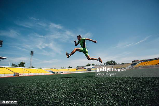 Full length of sporty young man running in stadium during training