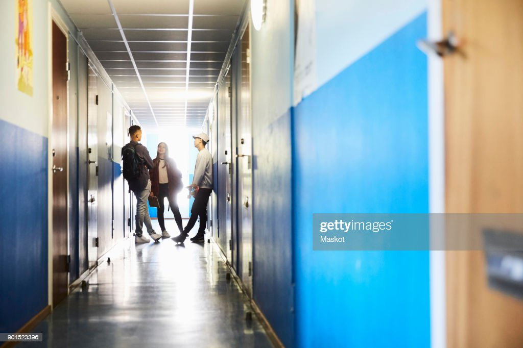 Full length of students talking while standing in corridor at university : Stock Photo