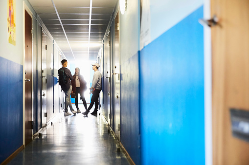 Full length of students talking while standing in corridor at university - gettyimageskorea