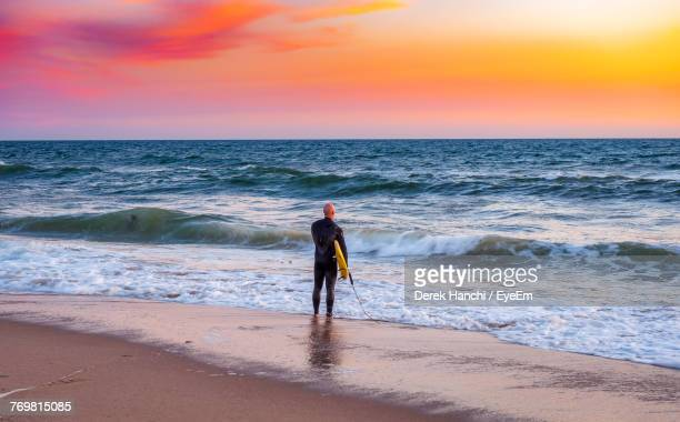 full length of surfer standing on sand at beach - hermosa beach stock pictures, royalty-free photos & images
