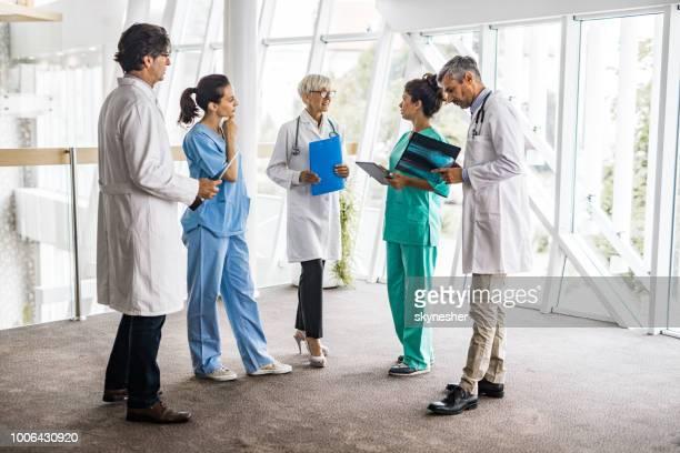 Volledige lengte van team van medisch deskundigen praten in een ziekenhuis.
