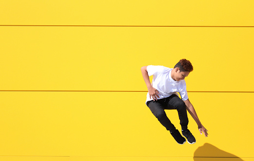 Full Length Of Teenage Boy Jumping By Yellow Wall - gettyimageskorea