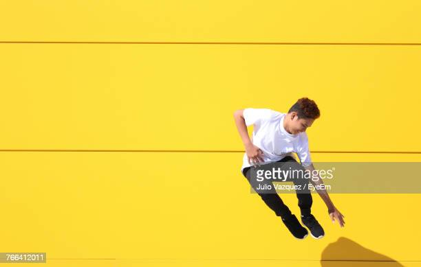 full length of teenage boy jumping by yellow wall - levendige kleur stockfoto's en -beelden
