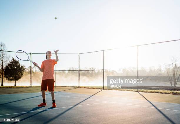 full length of teenage boy playing at tennis court - tennis player stock pictures, royalty-free photos & images