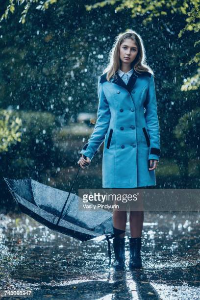 full length of teenage girl carrying umbrella standing on wet footpath in rain - alleen één tienermeisje stockfoto's en -beelden