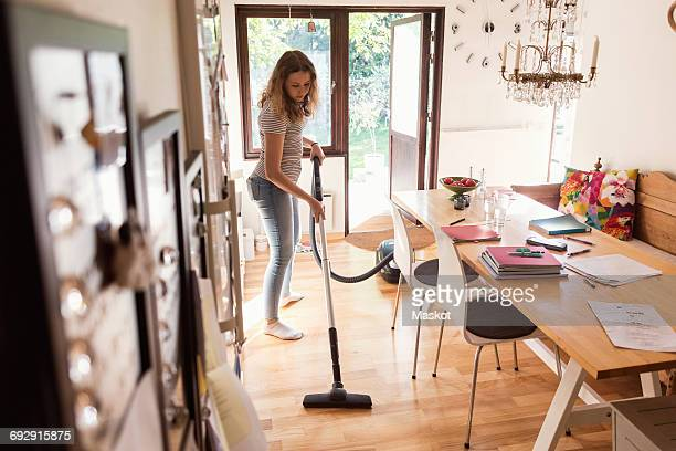 full length of teenage girl cleaning hardwood floor with vacuum cleaner at home - hausarbeit stock-fotos und bilder