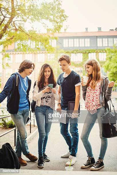 Full length of teenagers using smart phone on street
