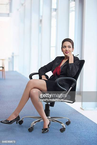 Full length of thoughtful businesswoman sitting on chair in office