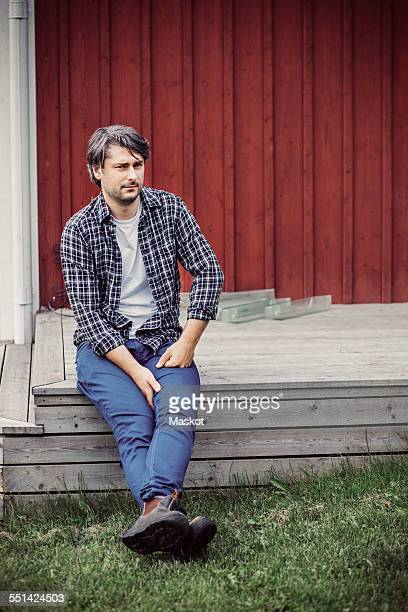 Full length of thoughtful male farmer sitting on porch at yard