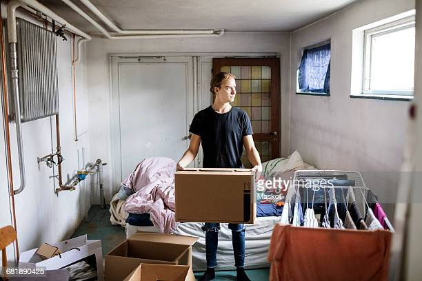Full length of thoughtful man carrying cardboard box while sanding in bedroom