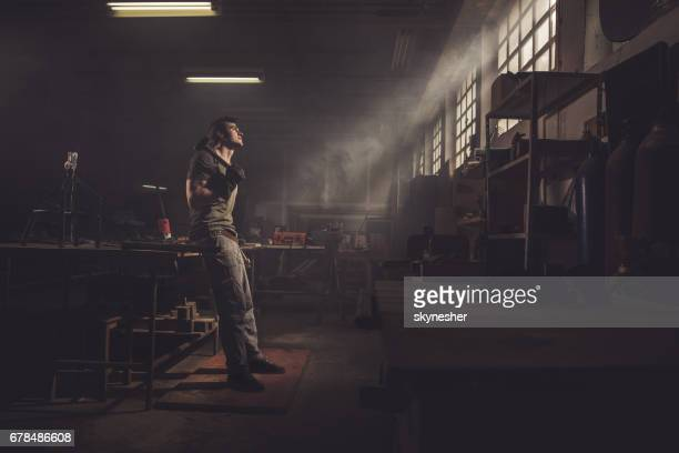Full length of thoughtful repairman with a hammer in a workshop.