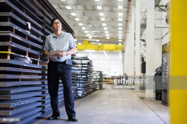 Full length of thoughtful supervisor writing on clipboard while standing by metal sheets at Steel Industry Factory