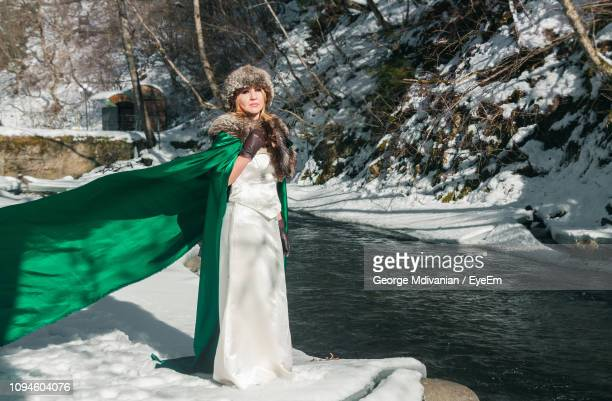 full length of thoughtful woman wearing animal boa while standing by river in forest during winter - flowing cape stock pictures, royalty-free photos & images