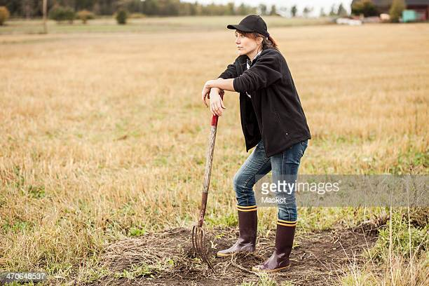 Full length of thoughtful woman with pitchfork standing at field