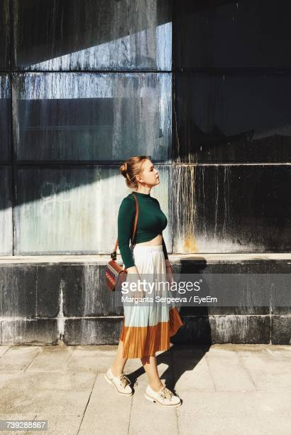 Full Length Of Thoughtful Young Woman Looking Away While Standing By Building