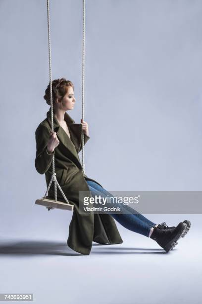 full length of thoughtful young woman sitting on swing against purple background - ブランコ ストックフォトと画像
