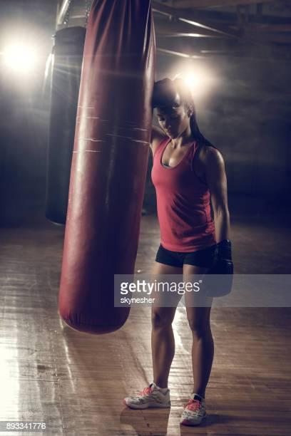comprimento total da mulher cansada construção muscular após o treino de boxe em um ginásio. - boxe feminino - fotografias e filmes do acervo