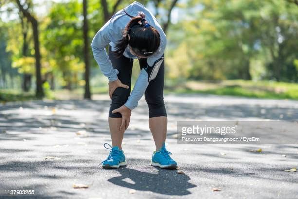 full length of tired woman touching knee in pain while standing on street - human knee stock pictures, royalty-free photos & images