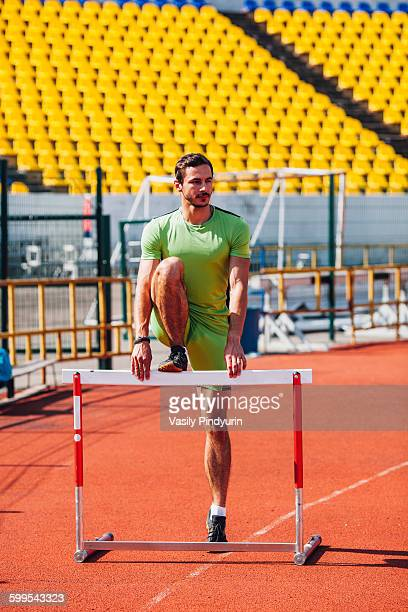 Full length of track and field athlete warming up on hurdle at sports track