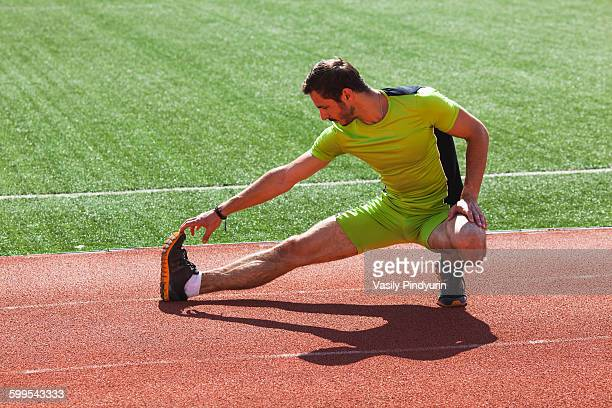 Full length of track and field athlete warming up on race track