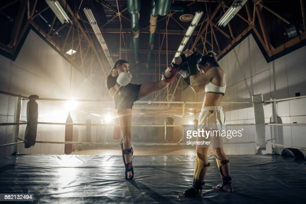 Full length of two athletic women on a kickboxing match in a ring.