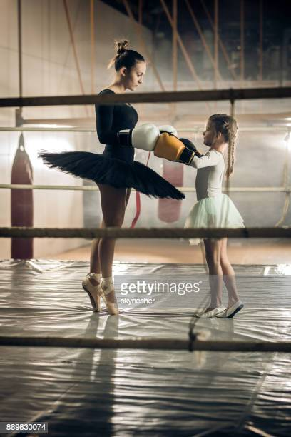 Full length of two ballerinas with boxing gloves in a ring.