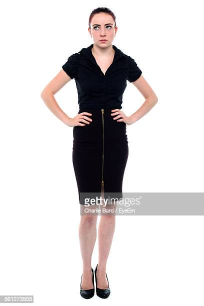 Full Length Of Upset Business Woman With Hands On Hip Standing Against White Background