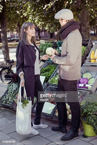 Full length of vendor showing vegetable to woman at market stall