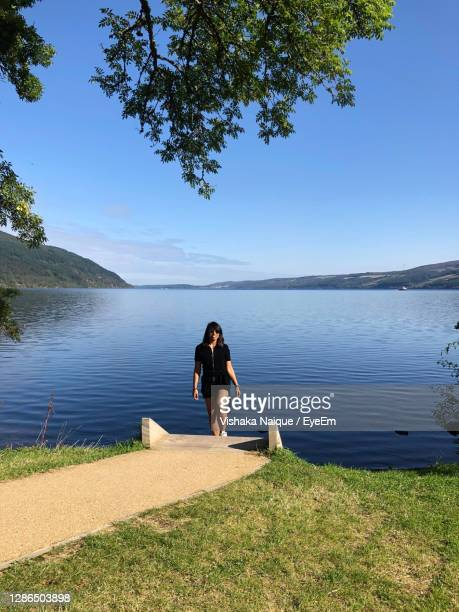 full length of woman by lake against sky - drumnadrochit stock pictures, royalty-free photos & images