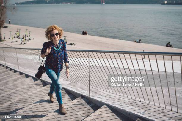 full length of woman climbing steps in city - bortes stock pictures, royalty-free photos & images