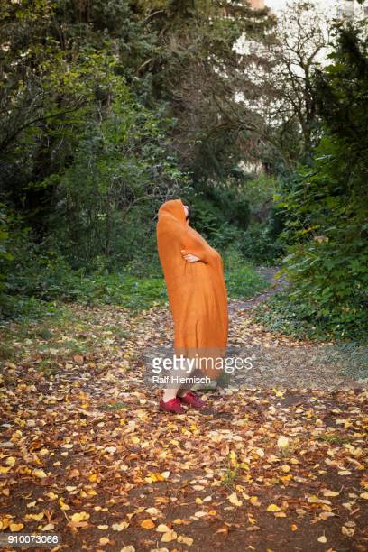 Full length of woman covered in orange scarf dancing at park during autumn