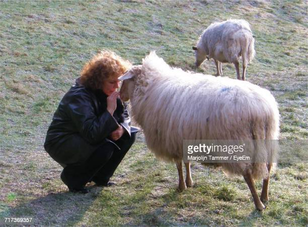 Full Length Of Woman Crouching By Sheep On Field