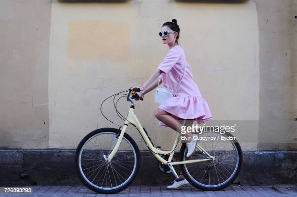 full length of woman cycling on road by wall - pink dress stock photos and pictures