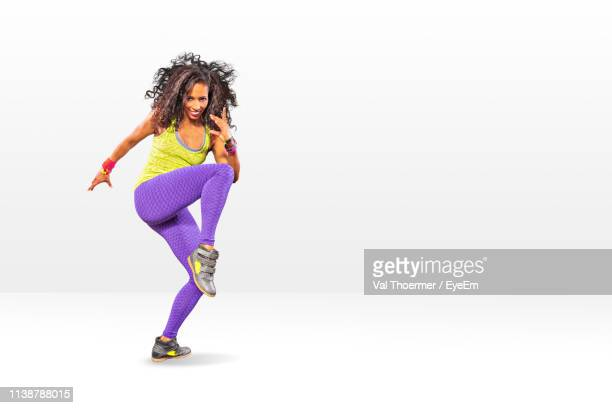 full length of woman dancing against white background - aerobics stock pictures, royalty-free photos & images