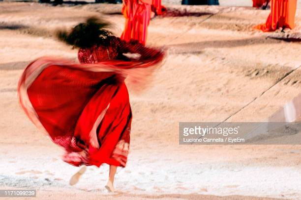 full length of woman dancing on sand at night - traditional ceremony stock pictures, royalty-free photos & images