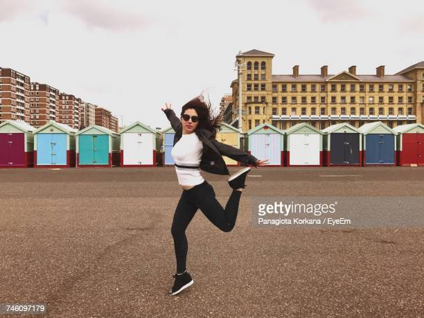 Full Length Of Woman Dancing On Street Against Beach Huts In City