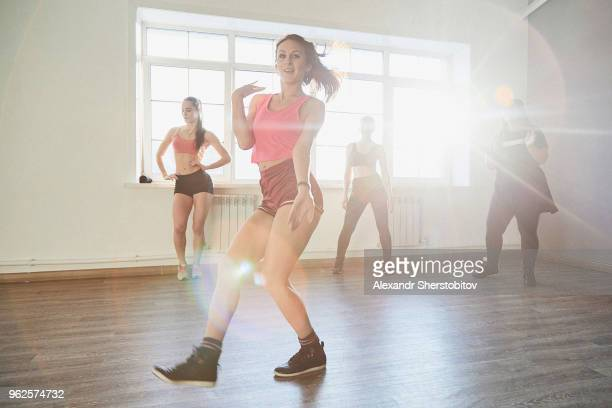 Full length of woman dancing while friends looking at studio on sunny day
