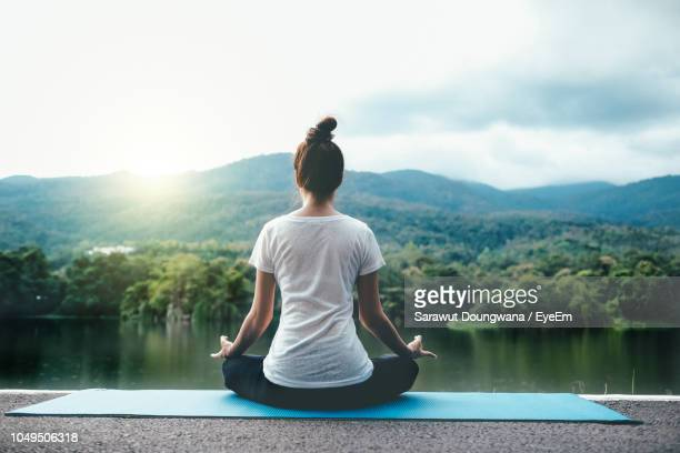 full length of woman doing yoga against lake - yoga fotografías e imágenes de stock