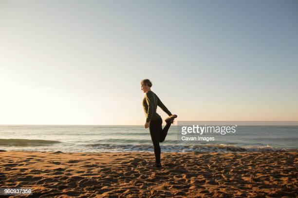 full length of woman doing yoga at beach against clear sky - céu claro imagens e fotografias de stock