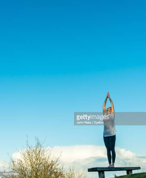 Full Length Of Woman Doing Yoga On Bench At Park Against Blue Sky