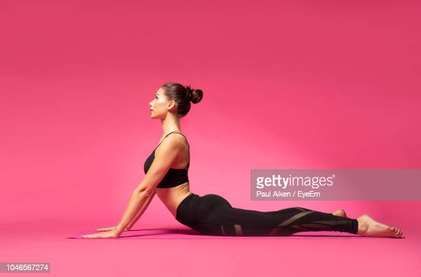 full length of woman doing yoga on pink background - aikāne stock pictures, royalty-free photos & images