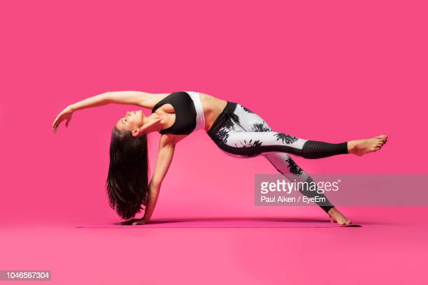 full length of woman doing yoga on pink background - adults only photos stock pictures, royalty-free photos & images