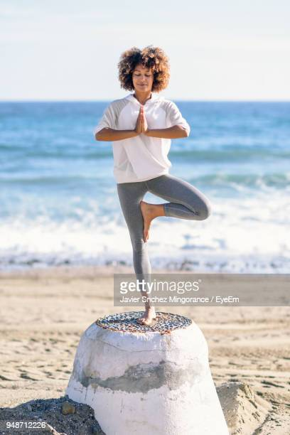 full length of woman doing yoga on rock at beach - standing on one leg stock pictures, royalty-free photos & images