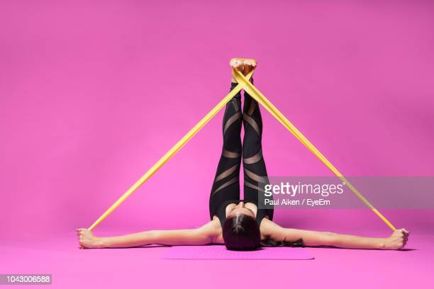 full length of woman doing yoga with rubber band on purple background - gummi stock-fotos und bilder