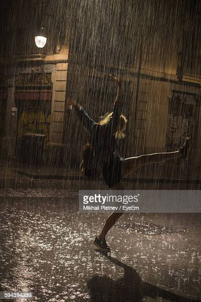 full length of woman enjoying in rain on street at night - rain stock pictures, royalty-free photos & images