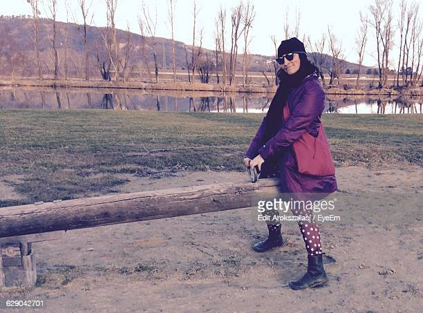 Full Length Of Woman Enjoying Seesaw On Field Against Sky